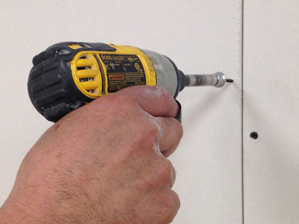 Installing Drywall using a drill.