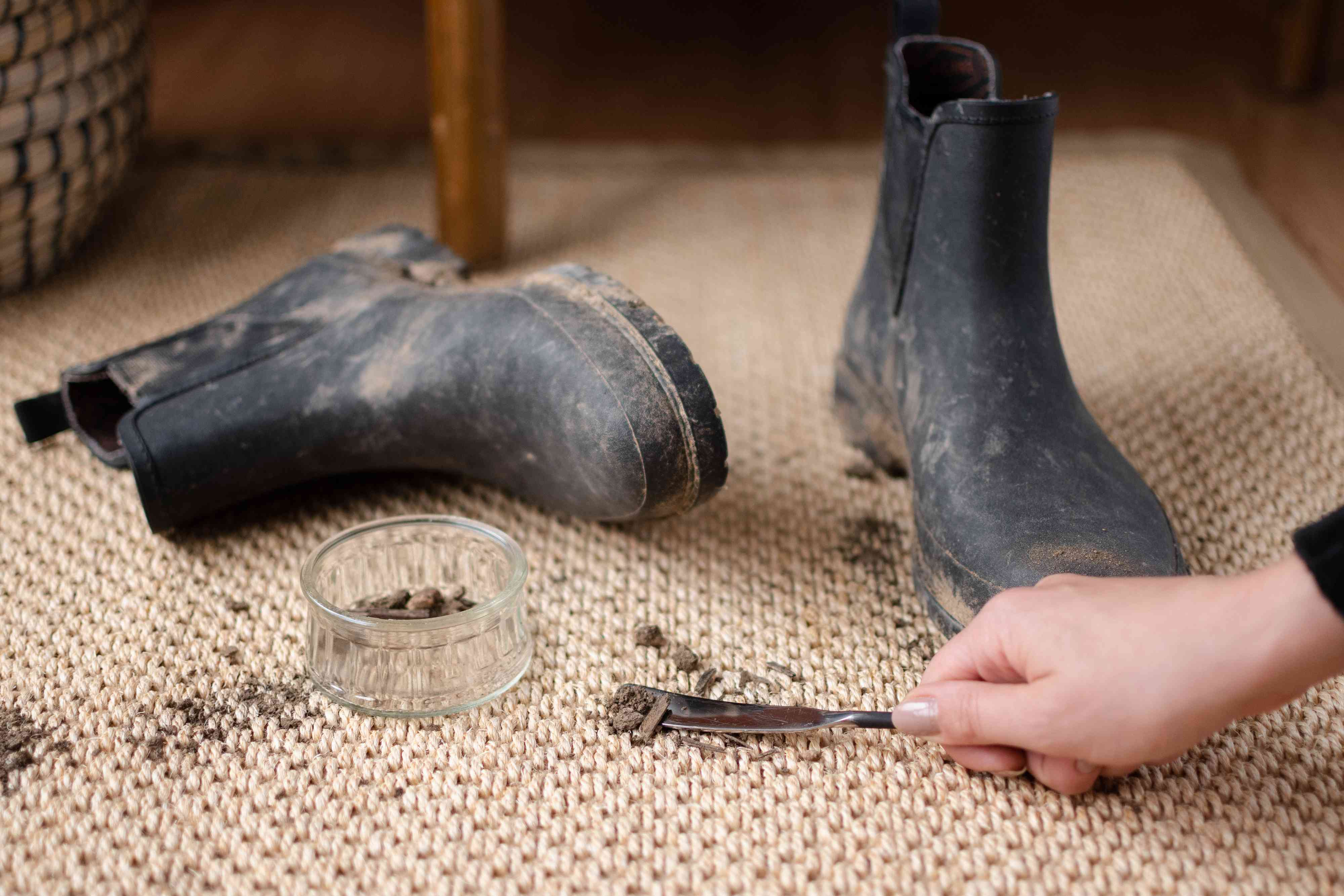 Dull knife scraping up dirt spills from mud covered boots on sisal rug