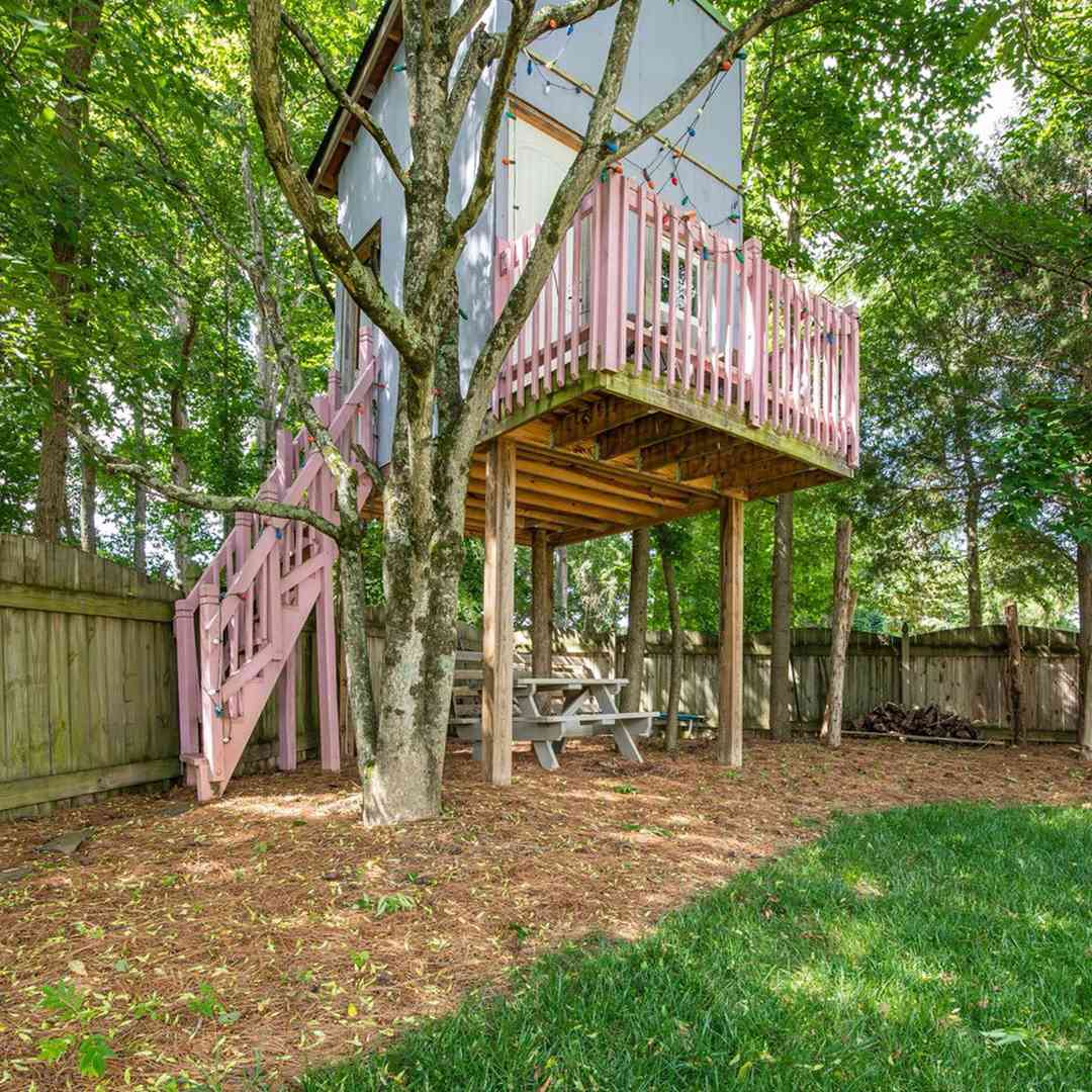 Treehouse with pink balcony in backyard