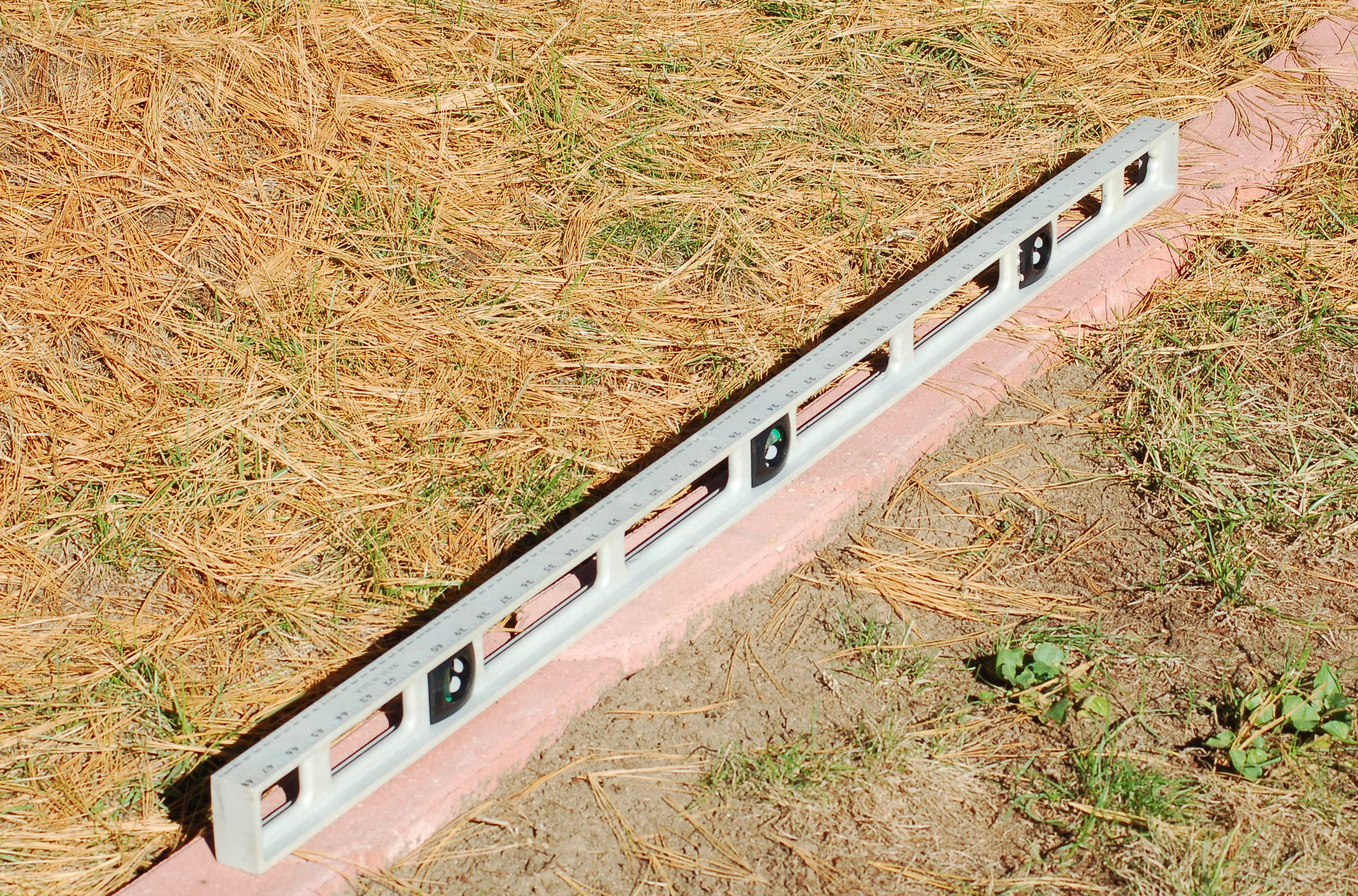 Using a carpenter's level to check that edging pavers are level