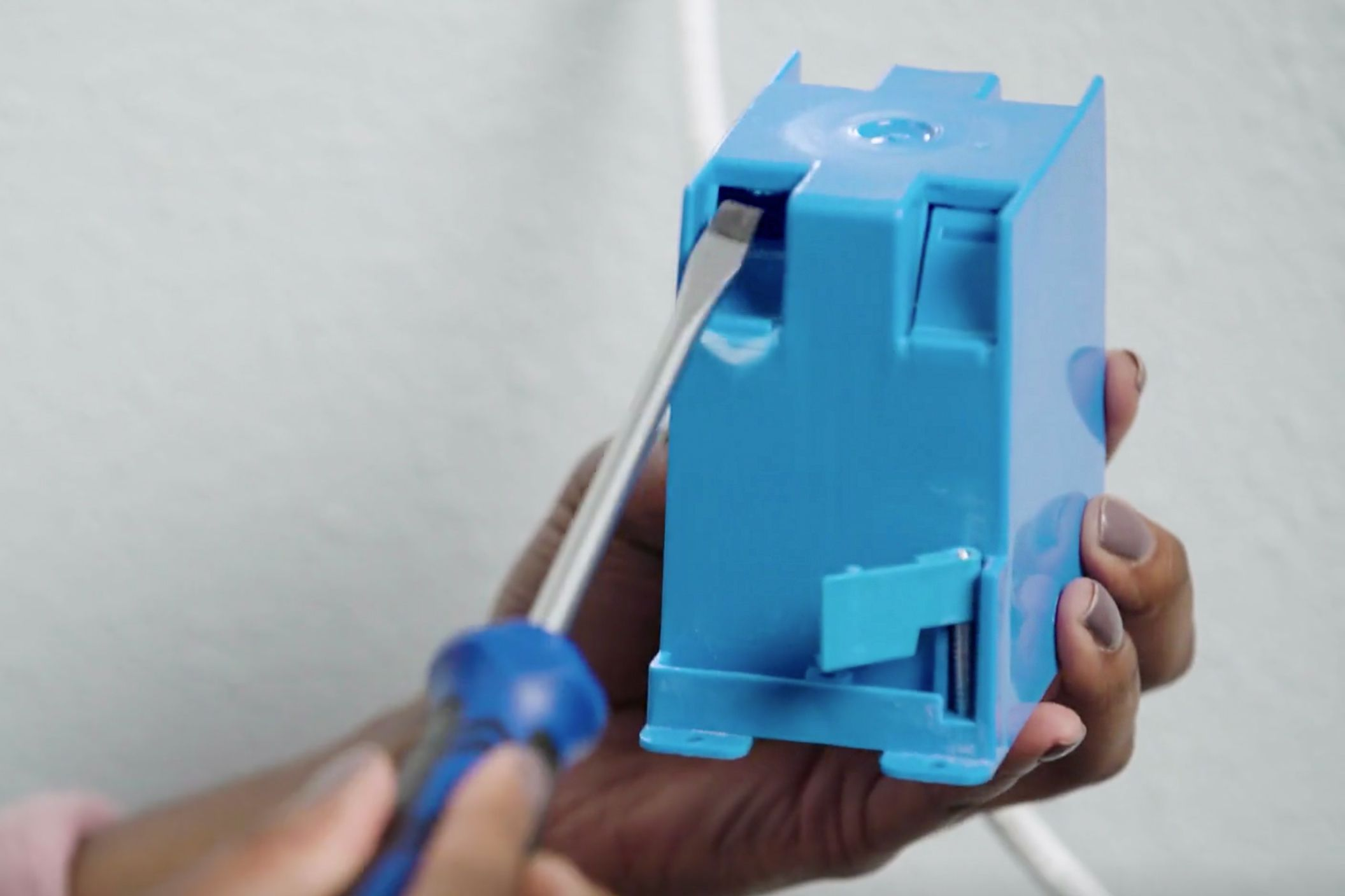 Cable clamp prepped on blue old work (retrofit) electrical box