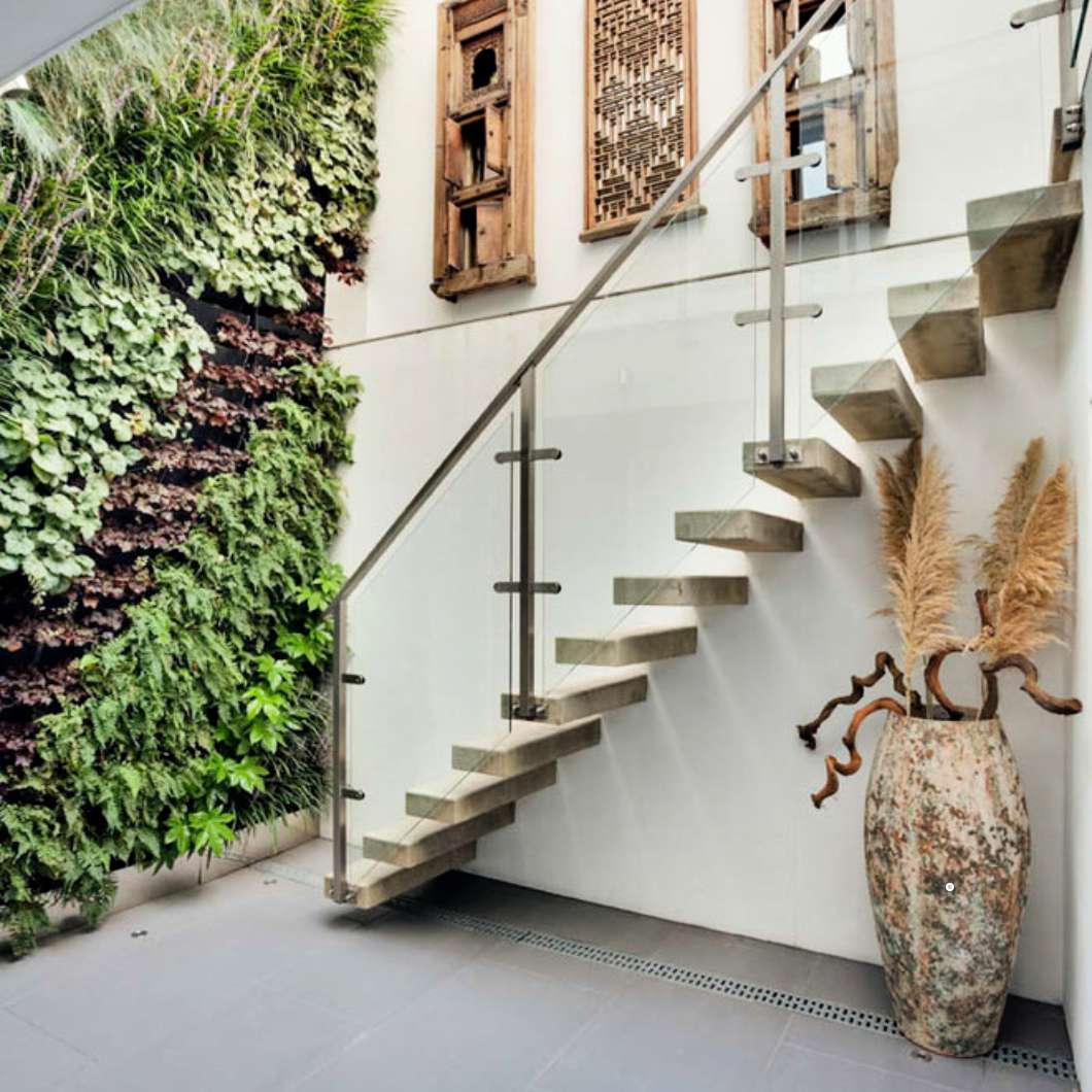 Vertical garden alongside stairs and house wall.