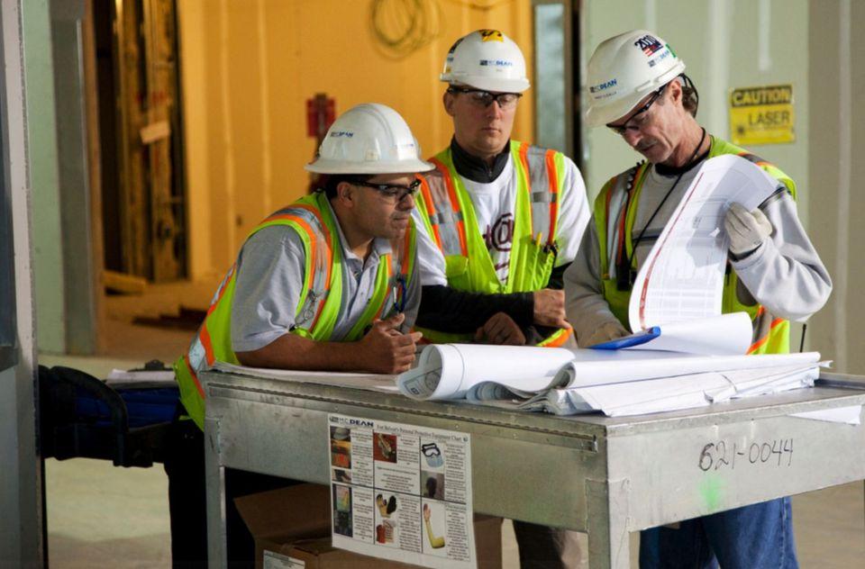 Building contractors examining blueprints