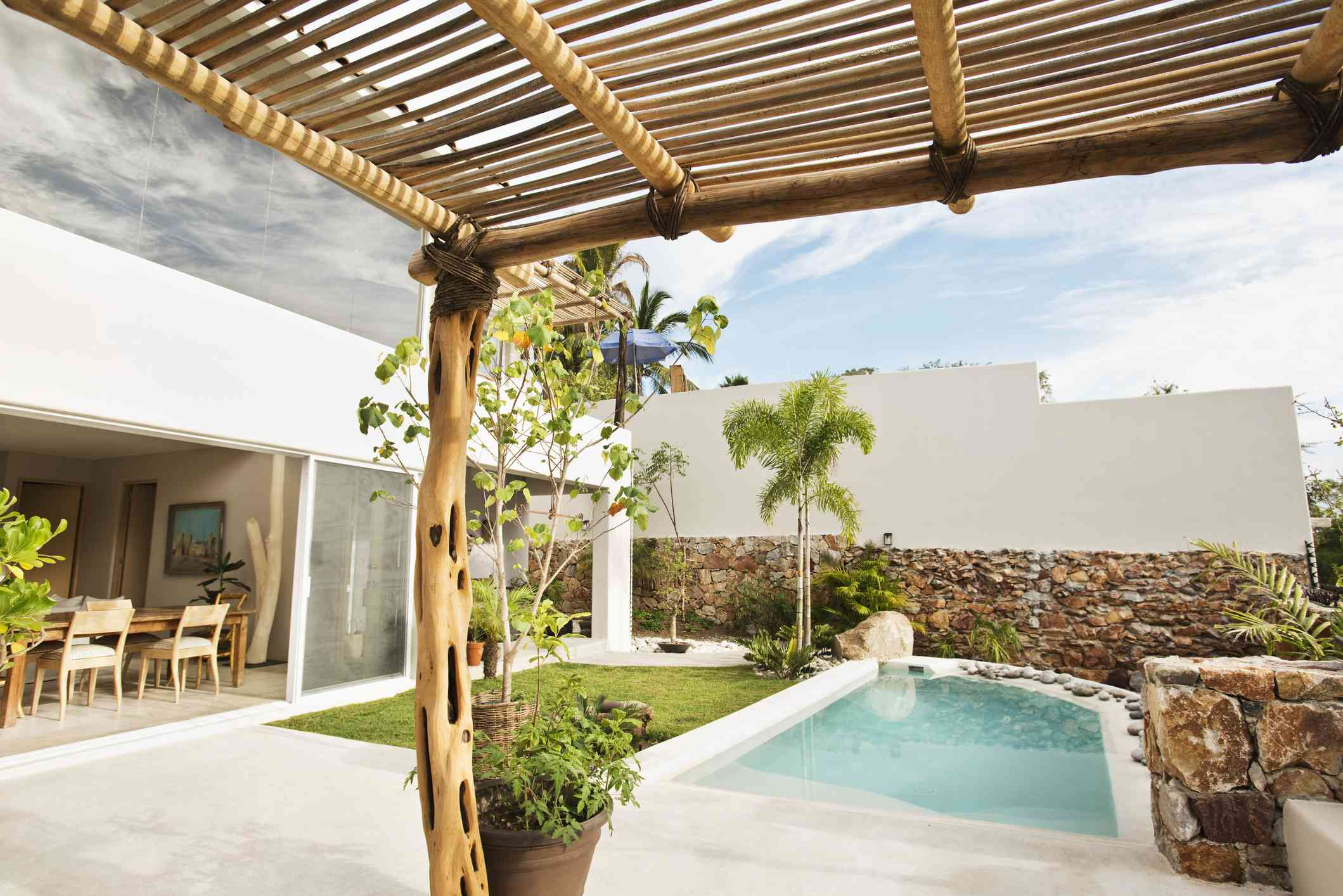 A view of a backyard pool with a short stone wall and a wooden pergola.