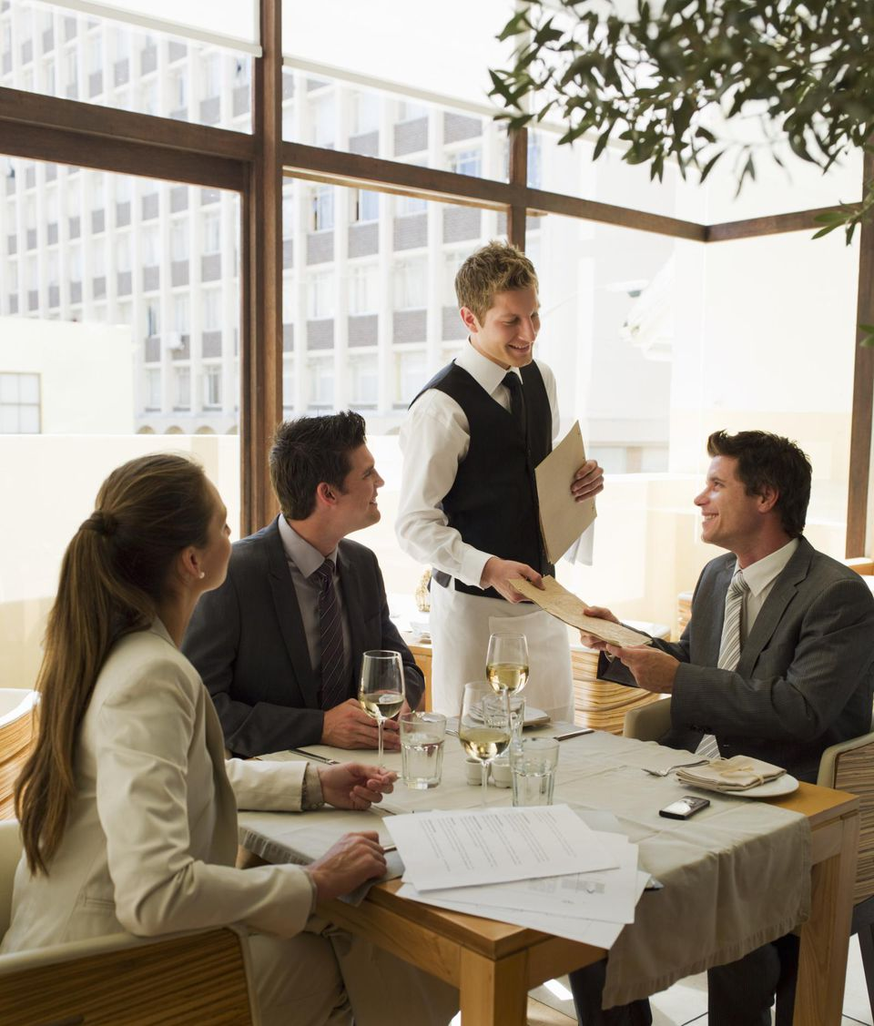 Waiter handing business people menus at restaurant table