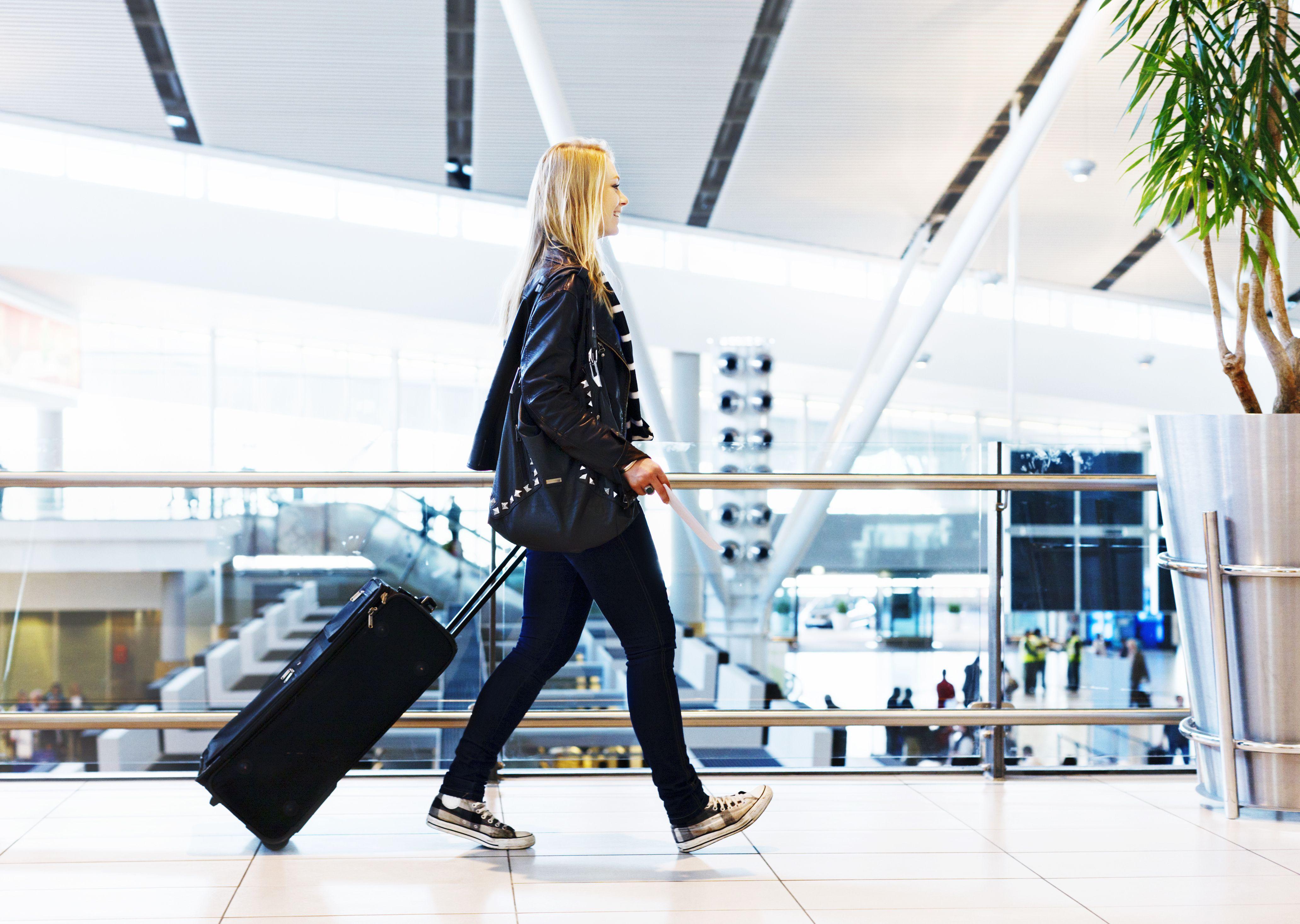 Feliz joven viajero remolcando el caso por el aeropuerto, sonriendo