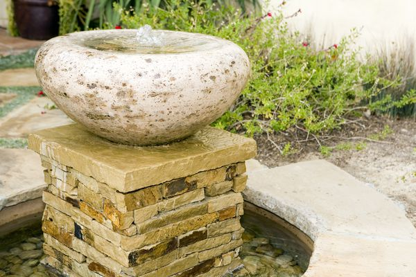 Stone fountain on patio with plants.