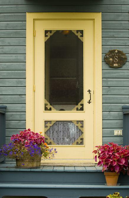 Una puerta de color amarillo pálido estilo granja en una casa azul grisácea