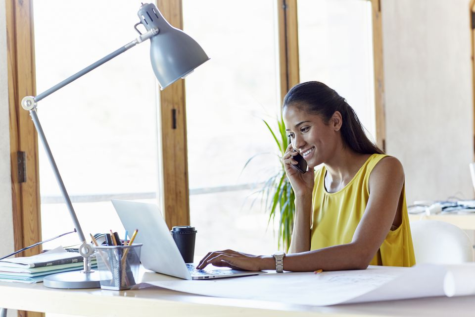 Smiling businesswoman using technologies in office