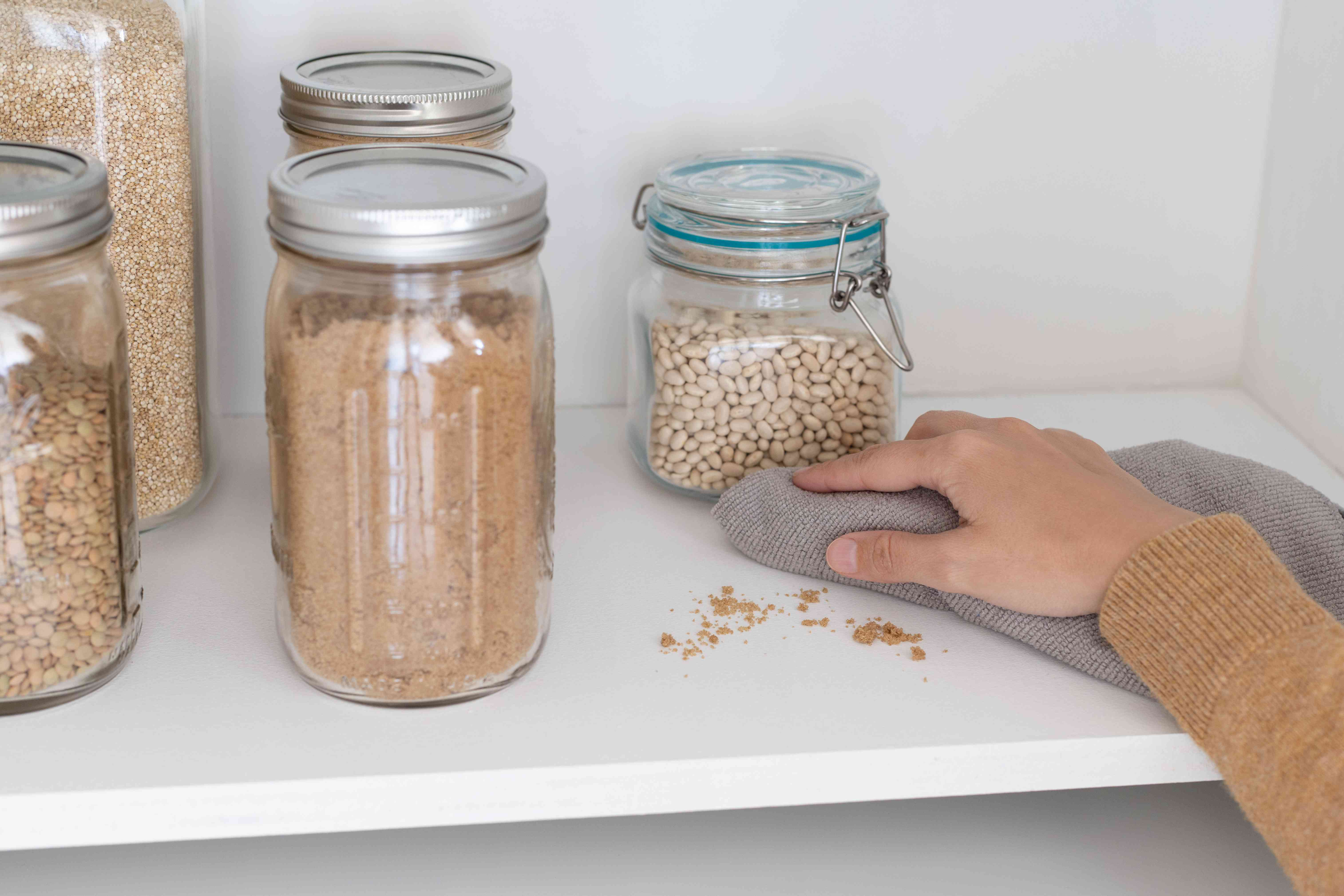 Spilled food crumbs on shelf being cleaned up with gray towel to prevent ants