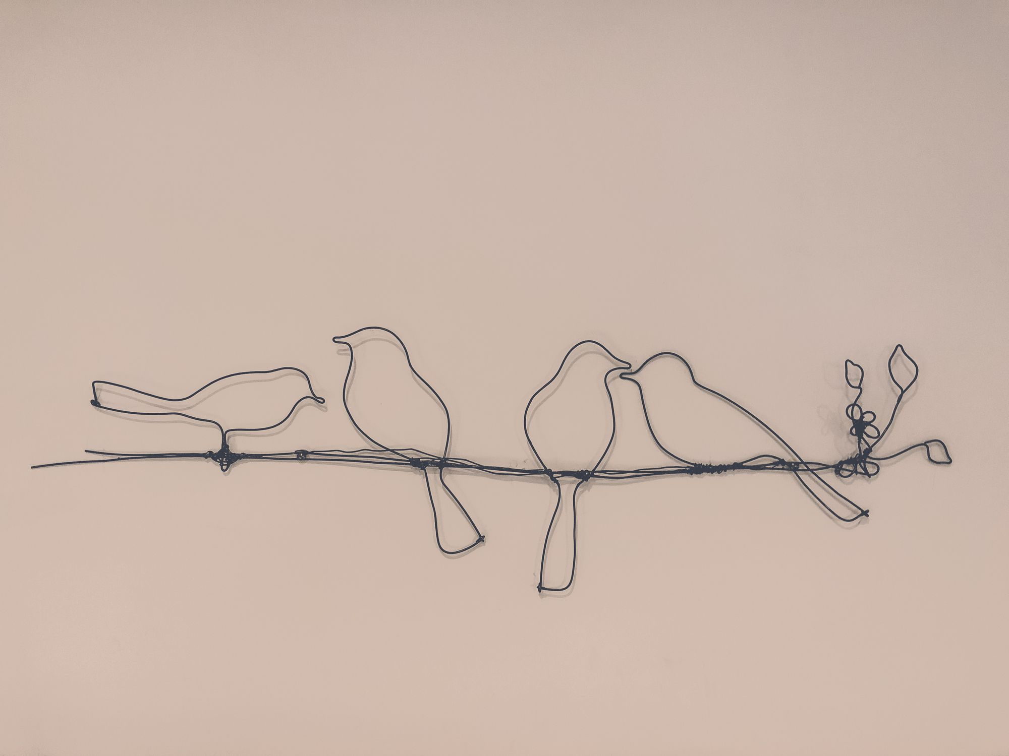 Abstract wire bird wall art mounted on a wall.