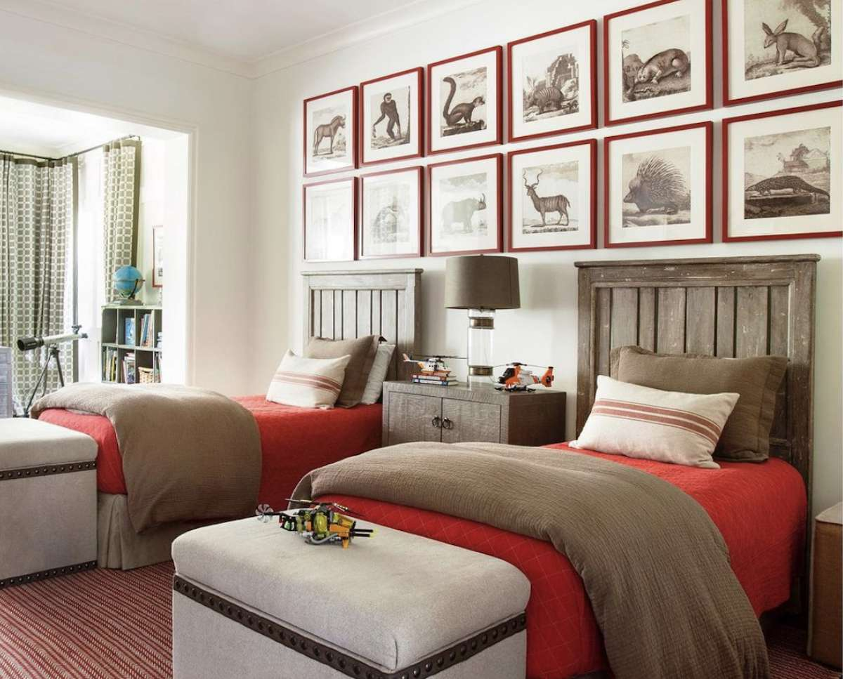 boy's bedroom with red bedsheets, medium wood tone headboard, white walls, gallery wall of red frames above bed