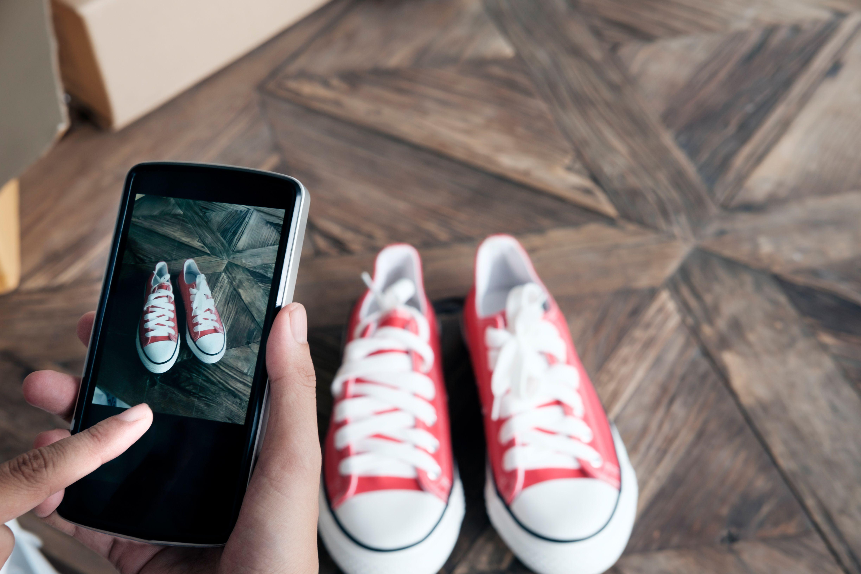 El vendedor en línea usa un teléfono móvil y toma una foto del producto para subirlo a la tienda en línea del sitio web