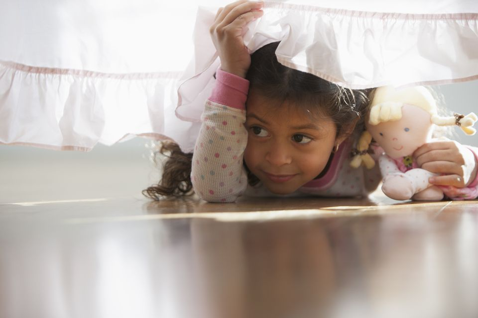 Hispanic girl crawling under bed