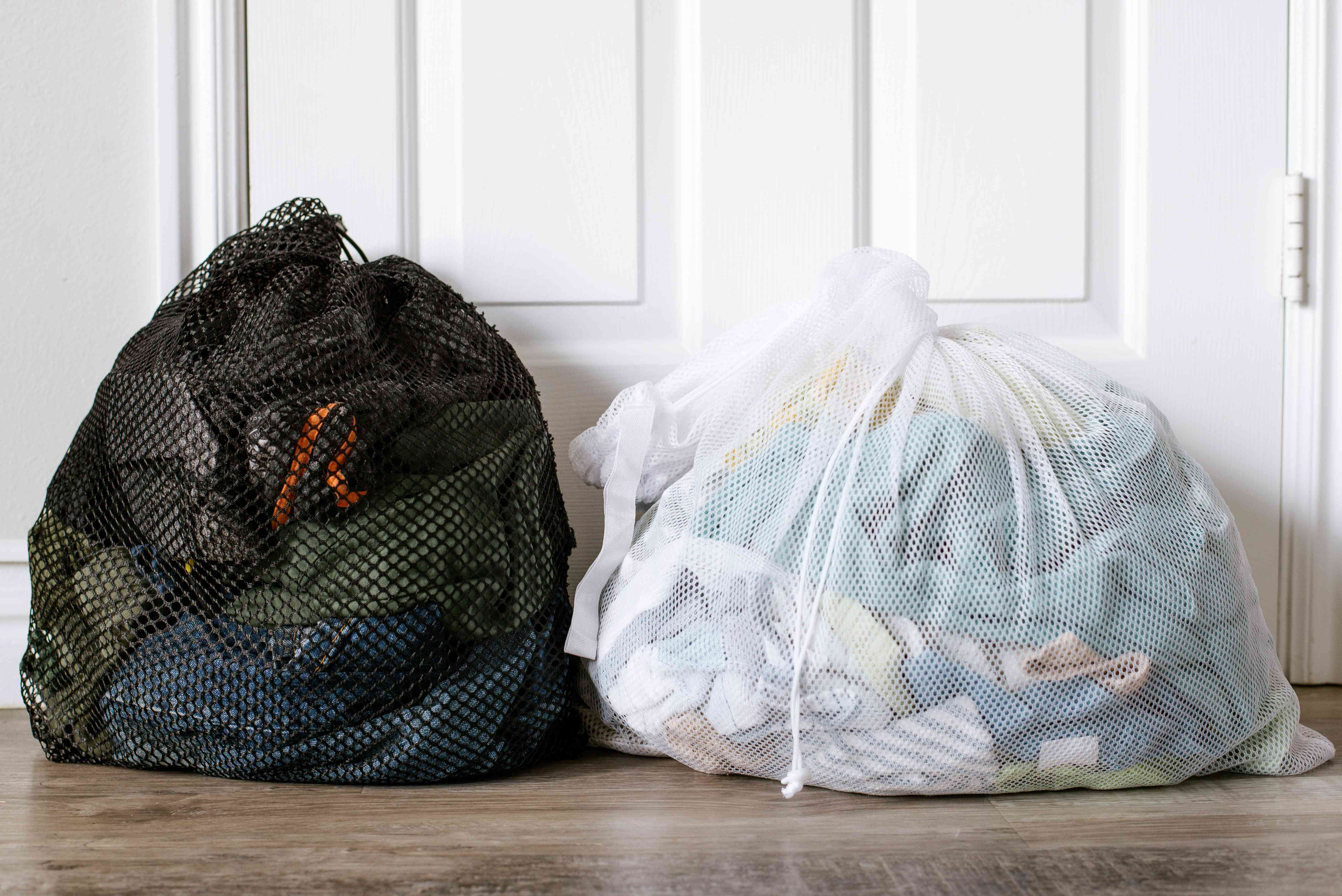 Clothes sorted in separate white and black laundry mesh bags for laundromat