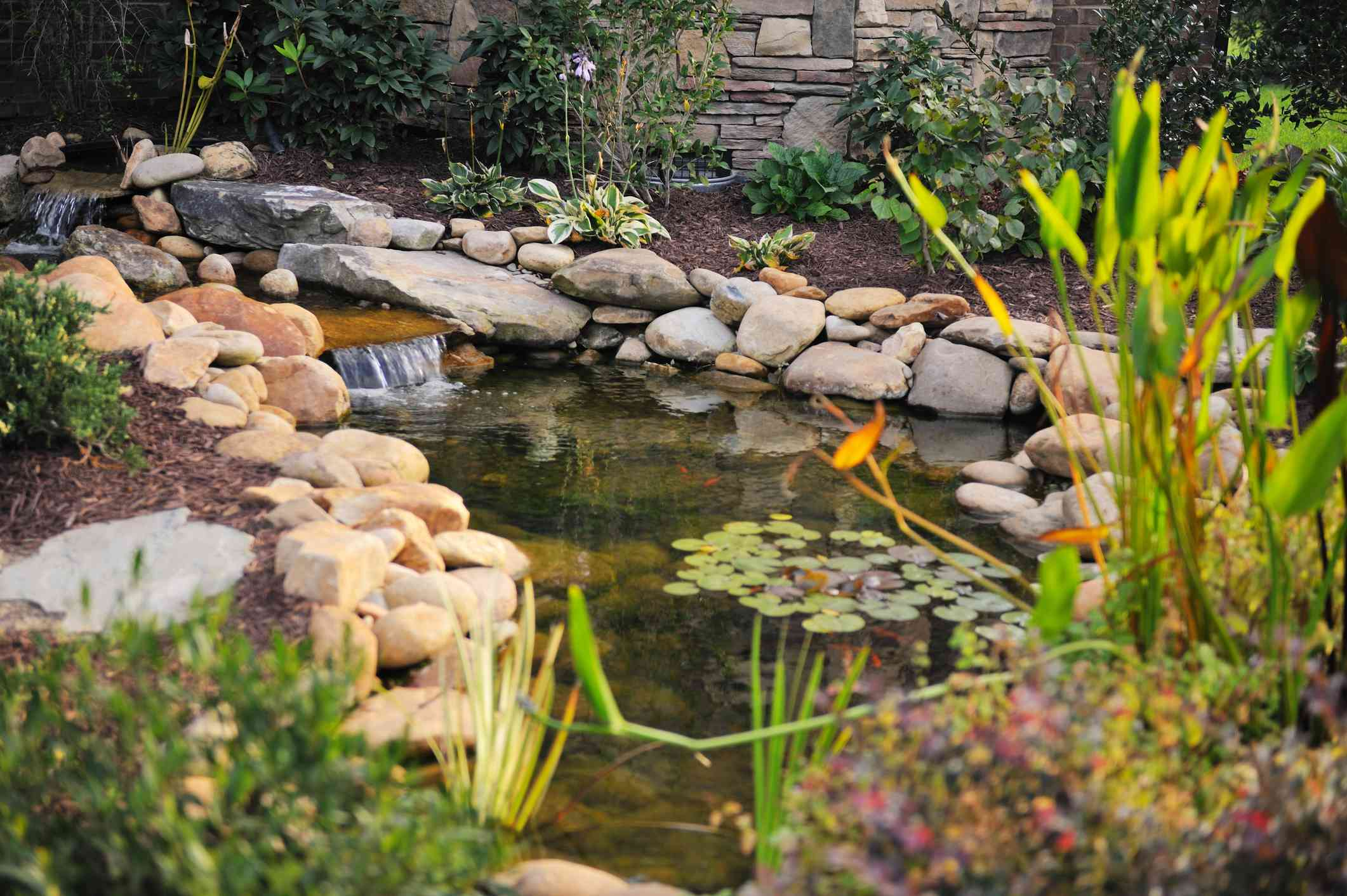A small koi pond bordered by rocks and a small waterfall.