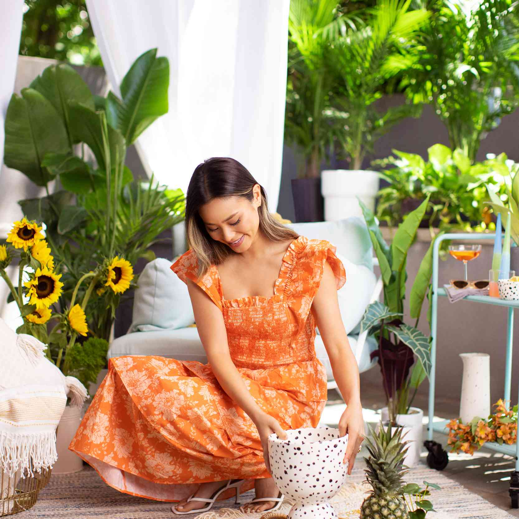 Jamie Chung arranges a tray of fruits and decor on a rug in her Brooklyn backyard