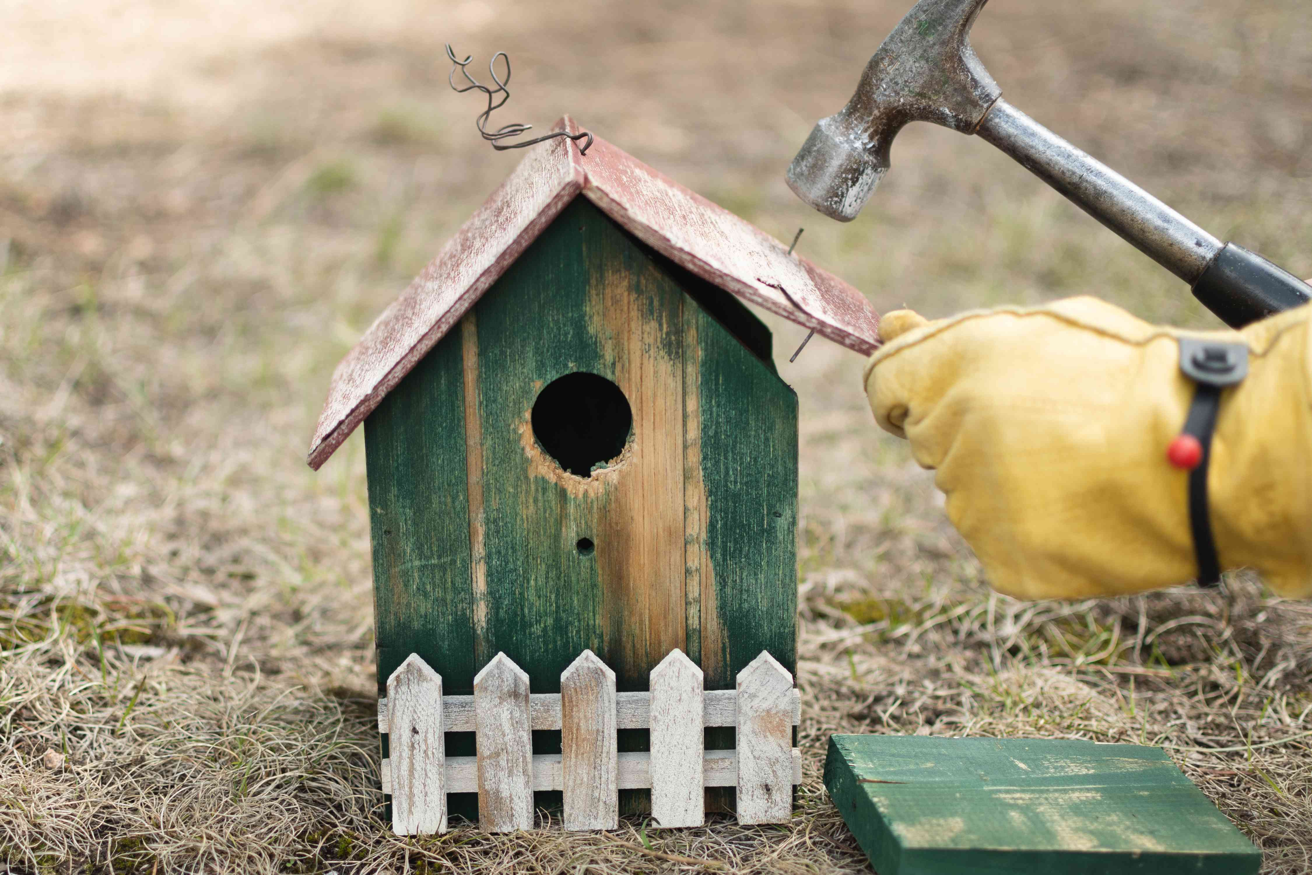 Loose hinges on birdhouse roof being fixed with hammer