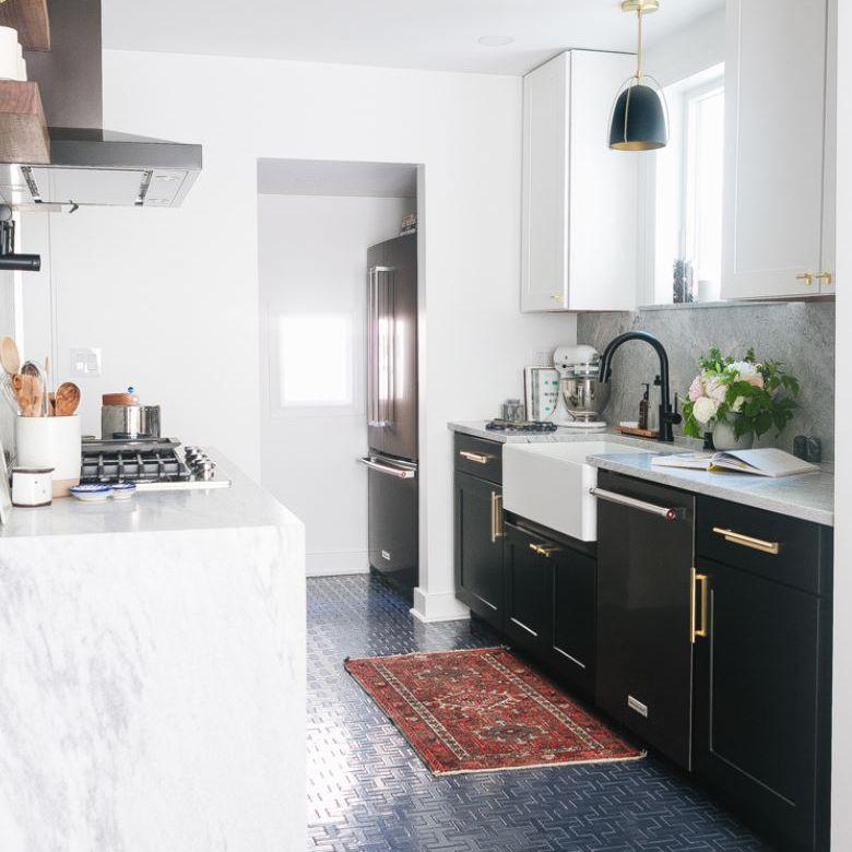 Cocina renovada con gabinetes inferiores negros, gabinetes superiores blancos y piso de baldosas azules