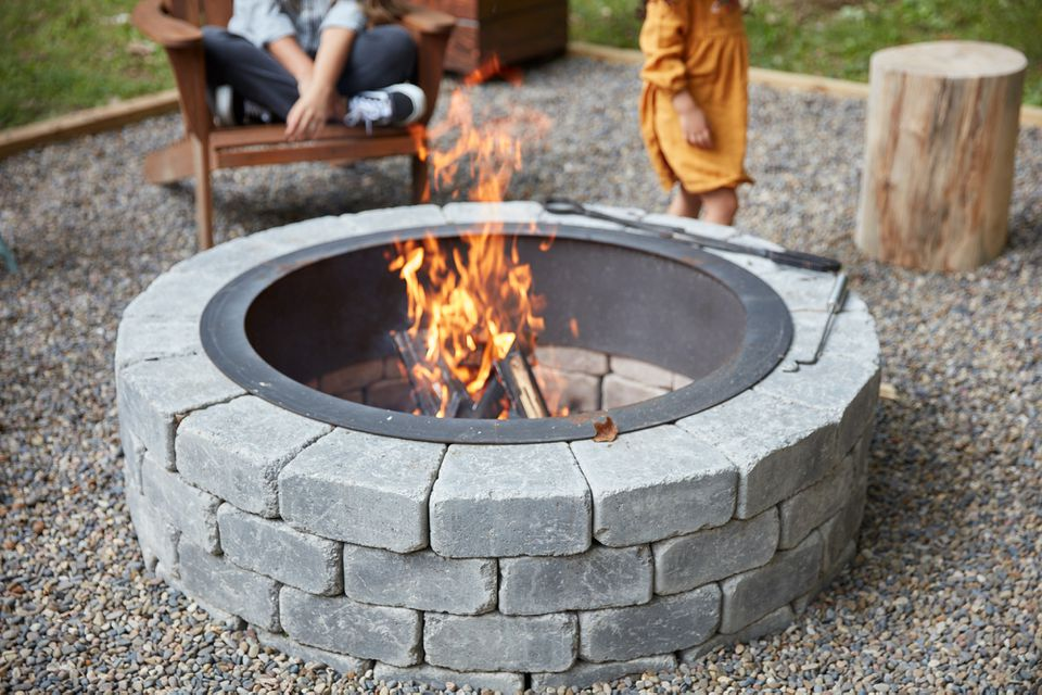 Circular fire pit with gray stones surrounding flame and pea gravel covering area