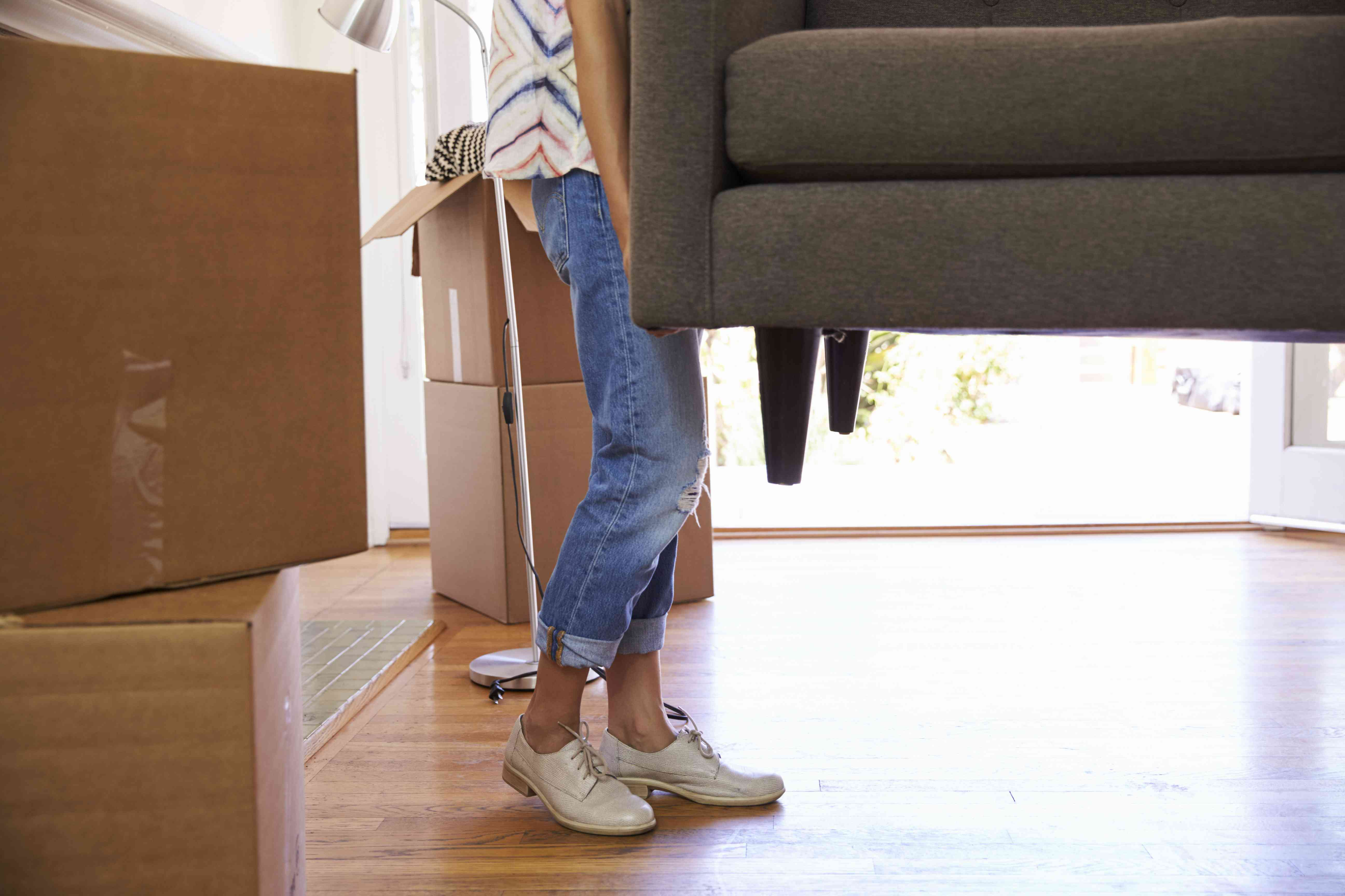 Close Up Of Woman Carrying Sofa Into New Home On Moving