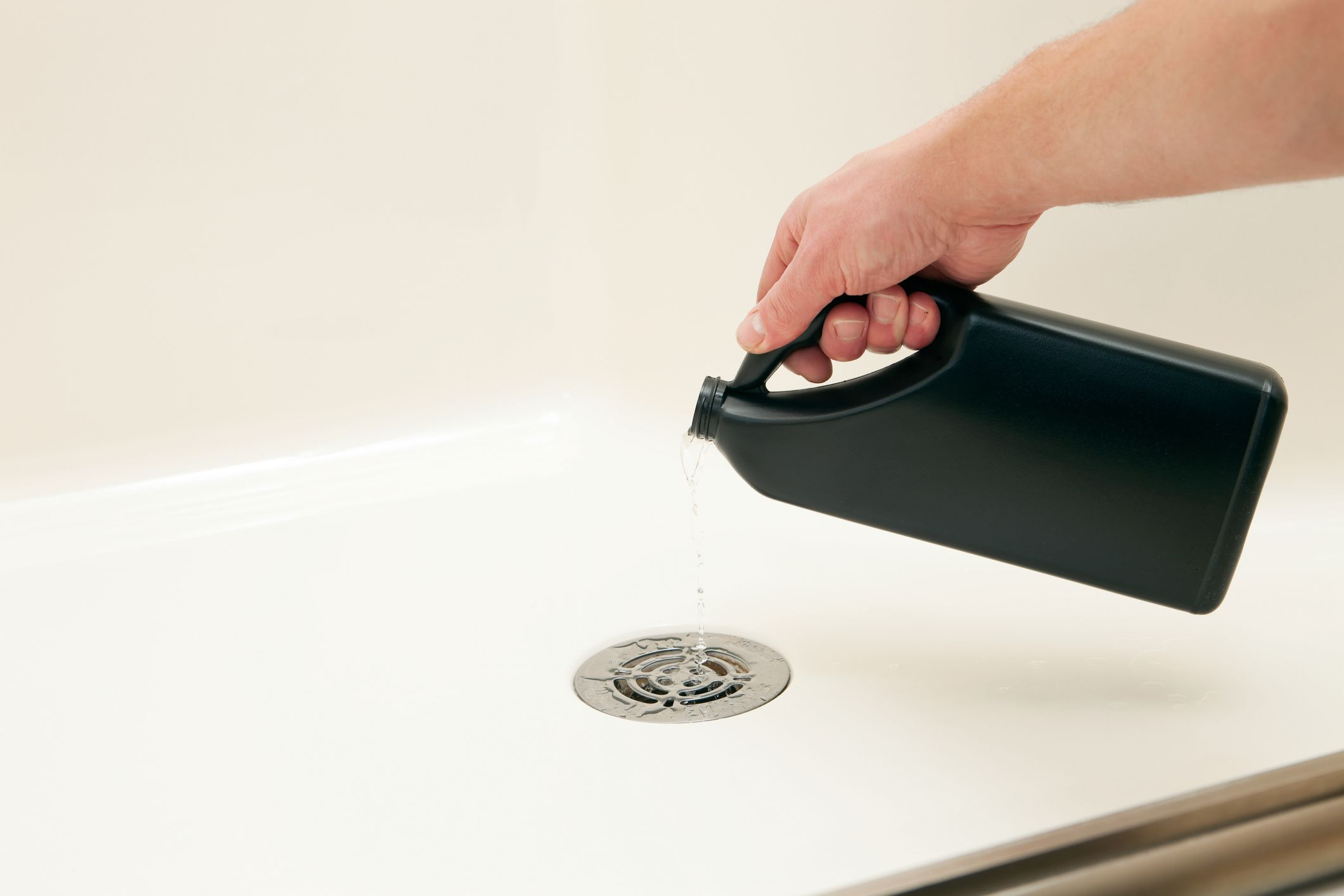 Unclogging Shower with Liquid Drain Cleaner 'A male hand is pouring liquid drain cleaner into a shower drain to dissolve a clog and improve water flow. Alternatively, this image could be used for poring waste down a drain.'