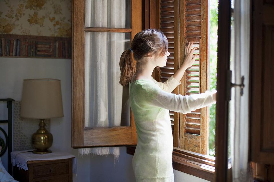 Young woman unshuttering the window