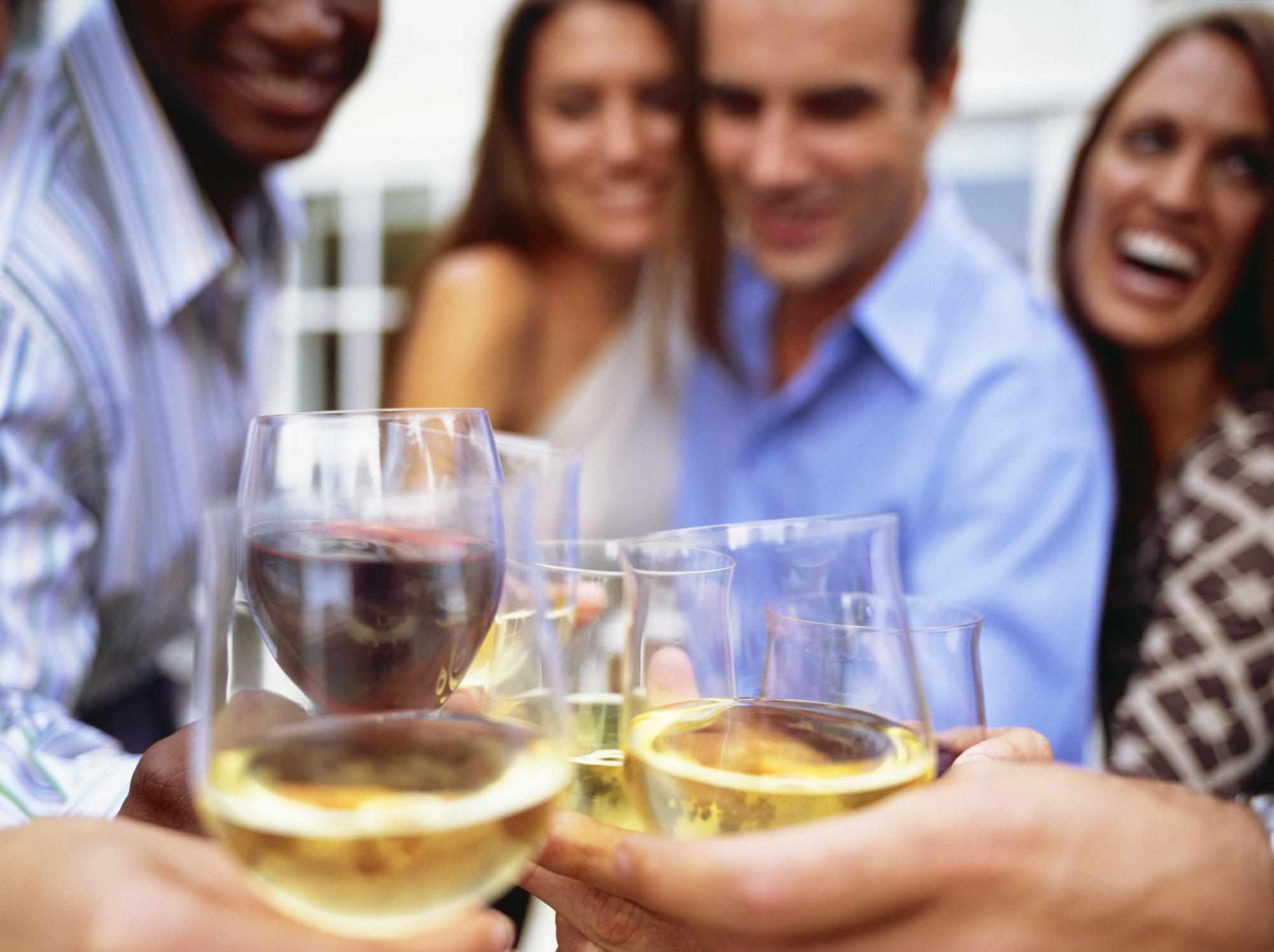 Two couples with each person holding a wine glass filled with white and red wine, and they're toasting the glasses.