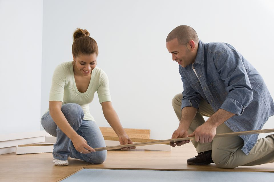 African American couple installing flooring