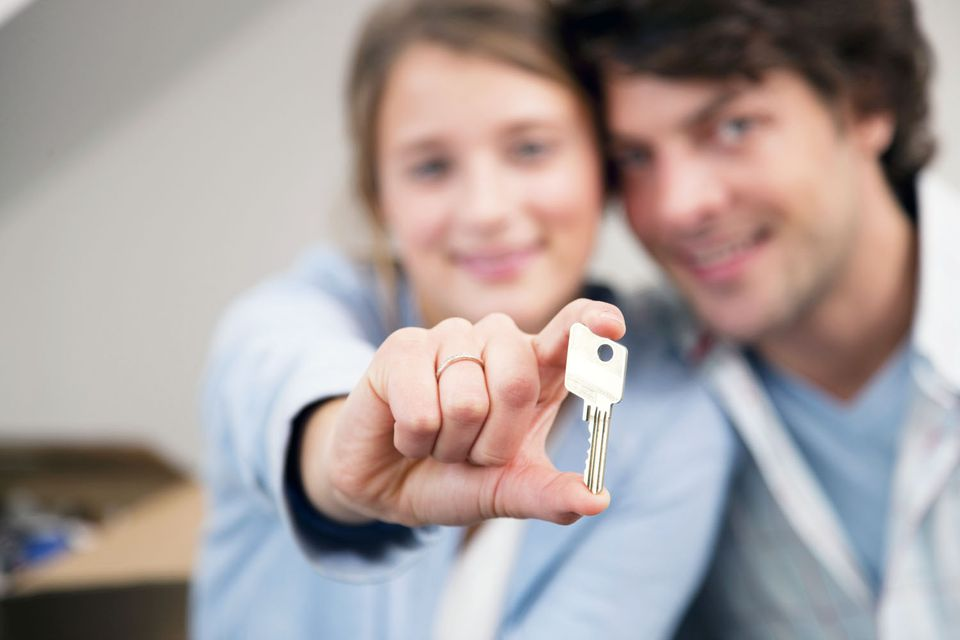 Happy couple holding a key to their new house
