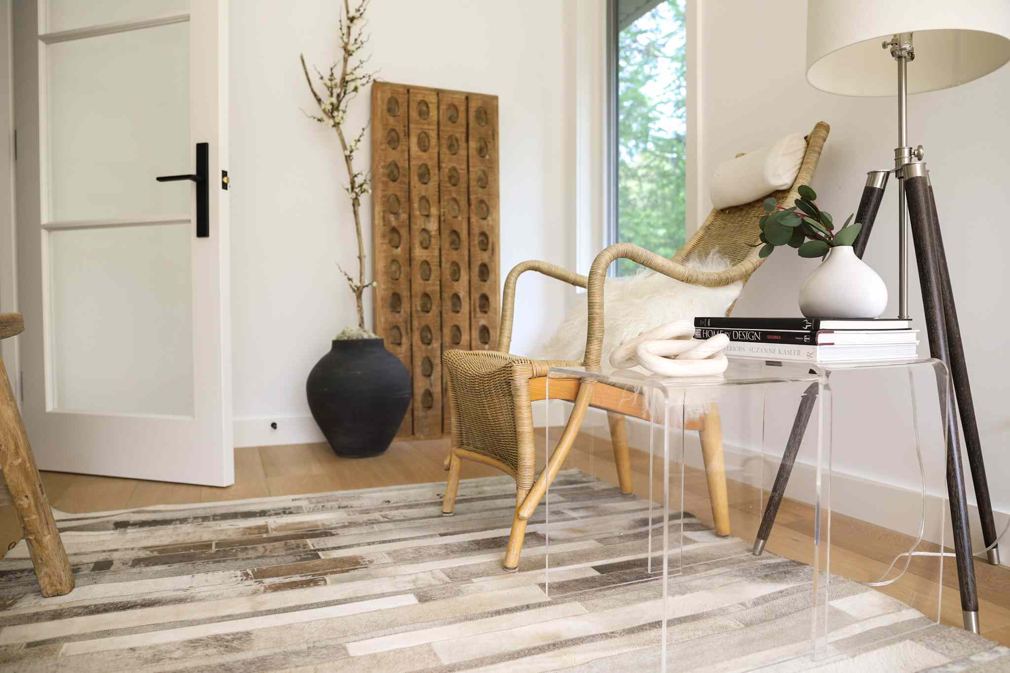 Wooden chair and glass side table moved out of the walk way with neutral-colored rug in middle