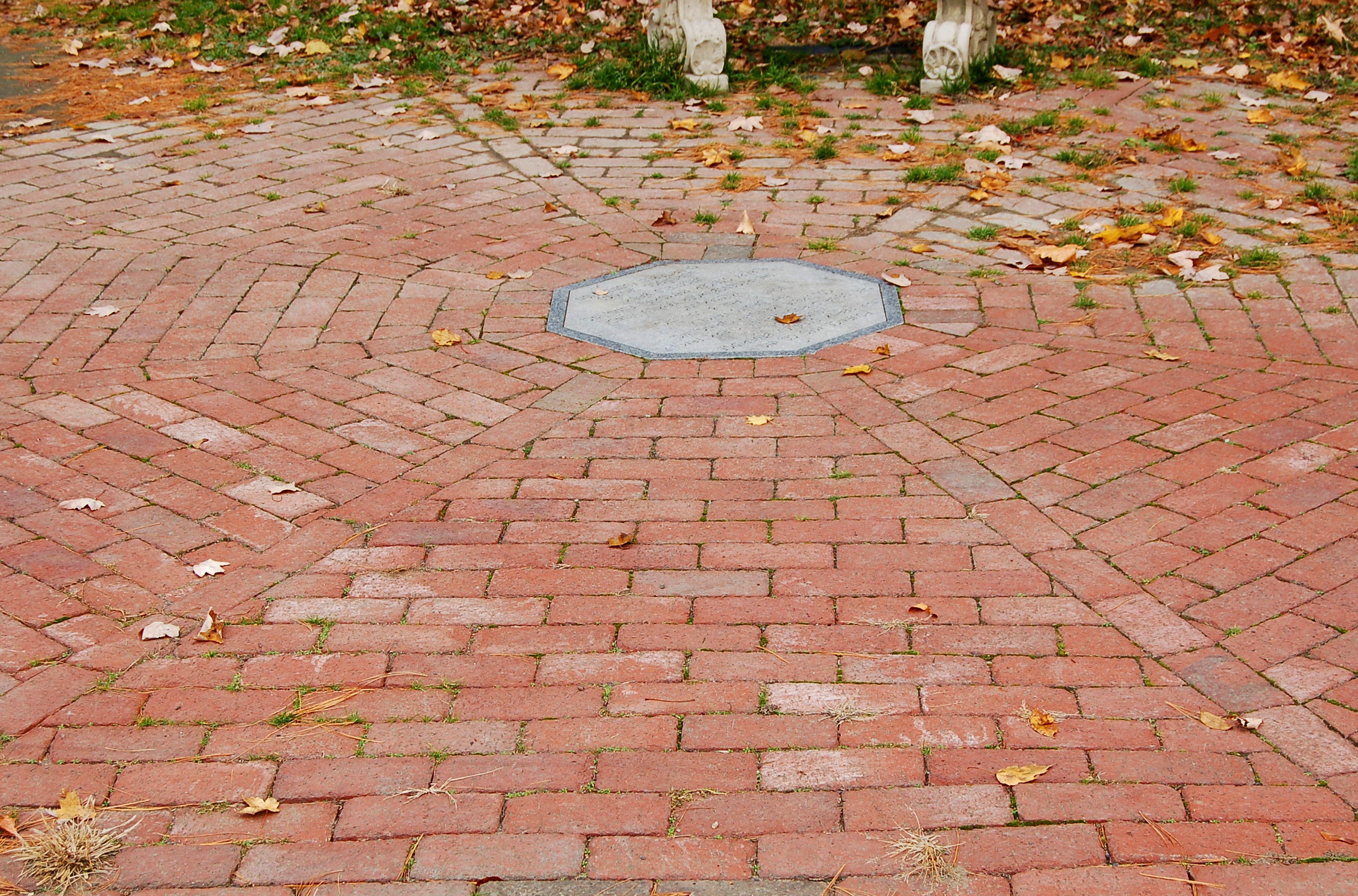 Patio circular de ladrillo con incrustaciones en el centro