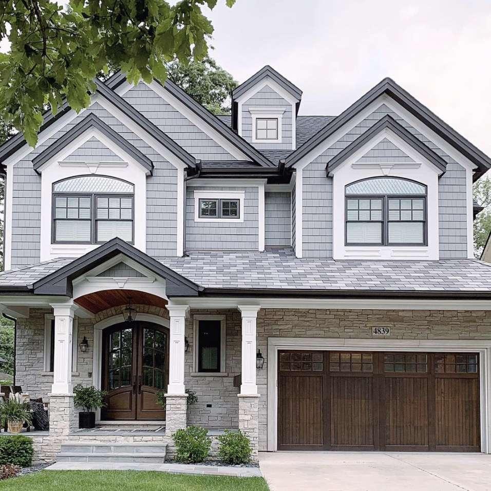 house with front yard and wooden front door, white columns. Wooden garage door.