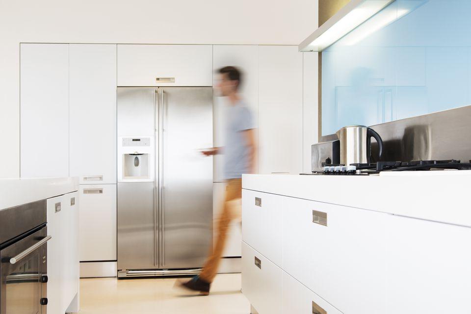 Man walking towards refrigerator in his modern kitchen