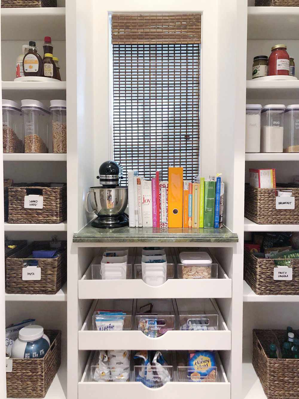 pantry with organized shelves, baskets and a table for cookbooks