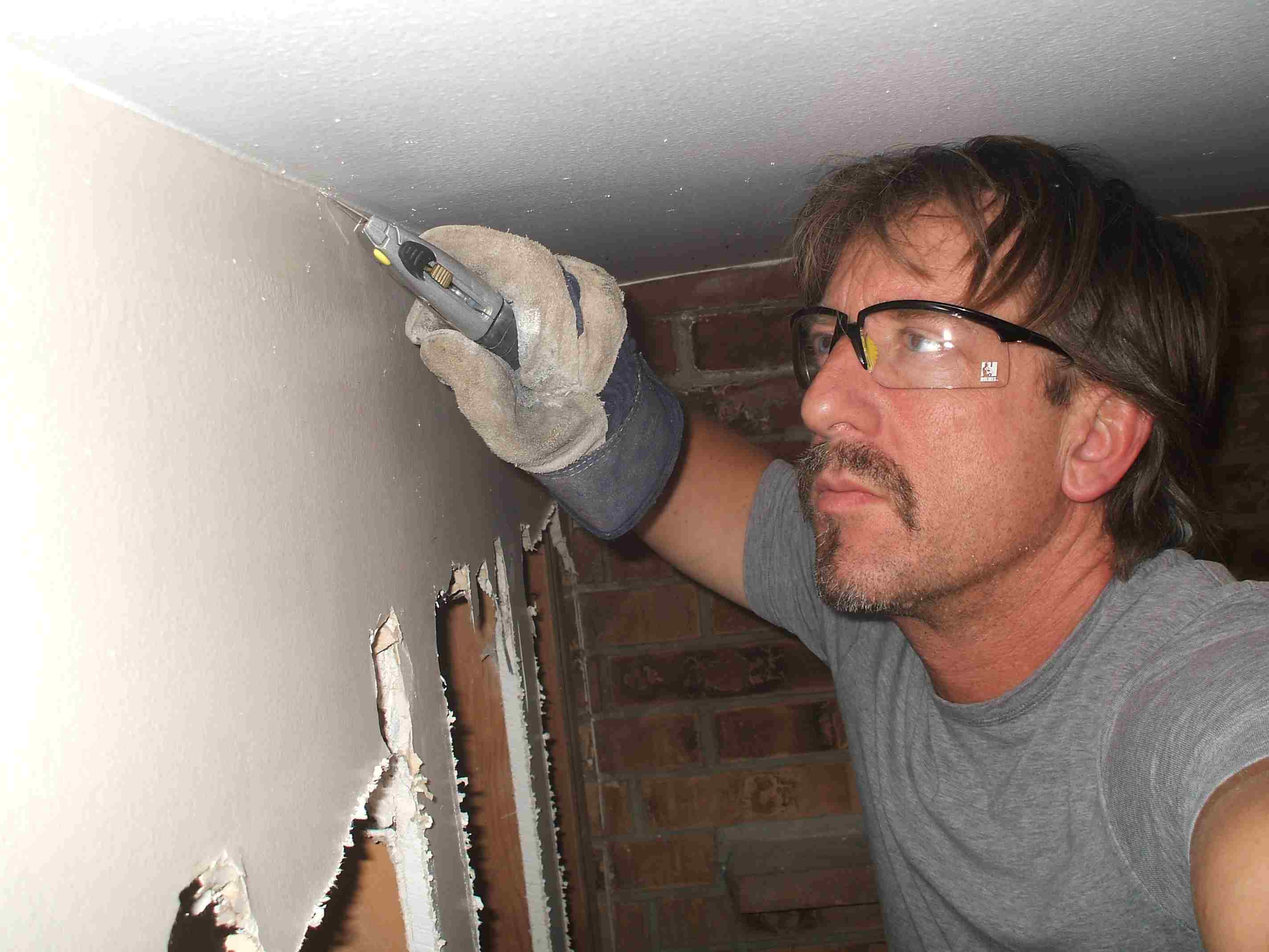 Cutting the paint and caulk off an interior wall