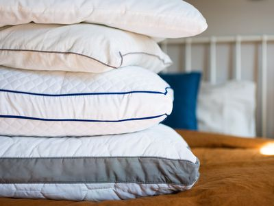 Pillows without sheets stacked on each other on top of bed
