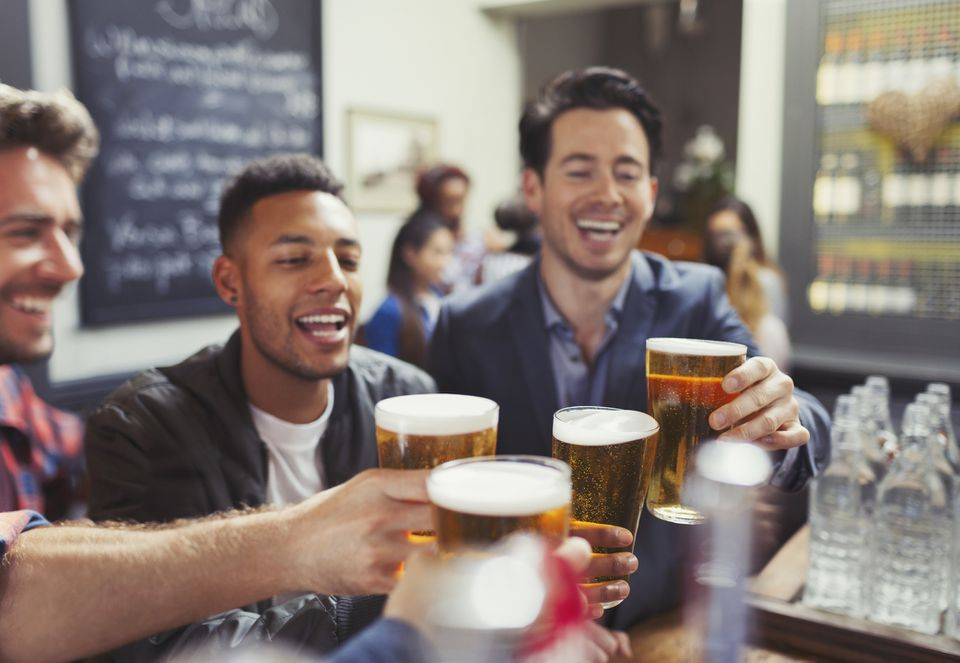 Young men toasting beer at a bar