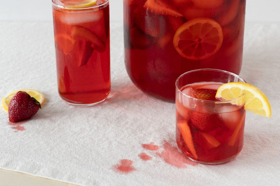 Fruit punch in drinking glasses and pitcher on white fabric with red stains