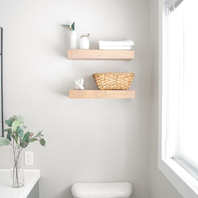 A bathroom with two floating shelves
