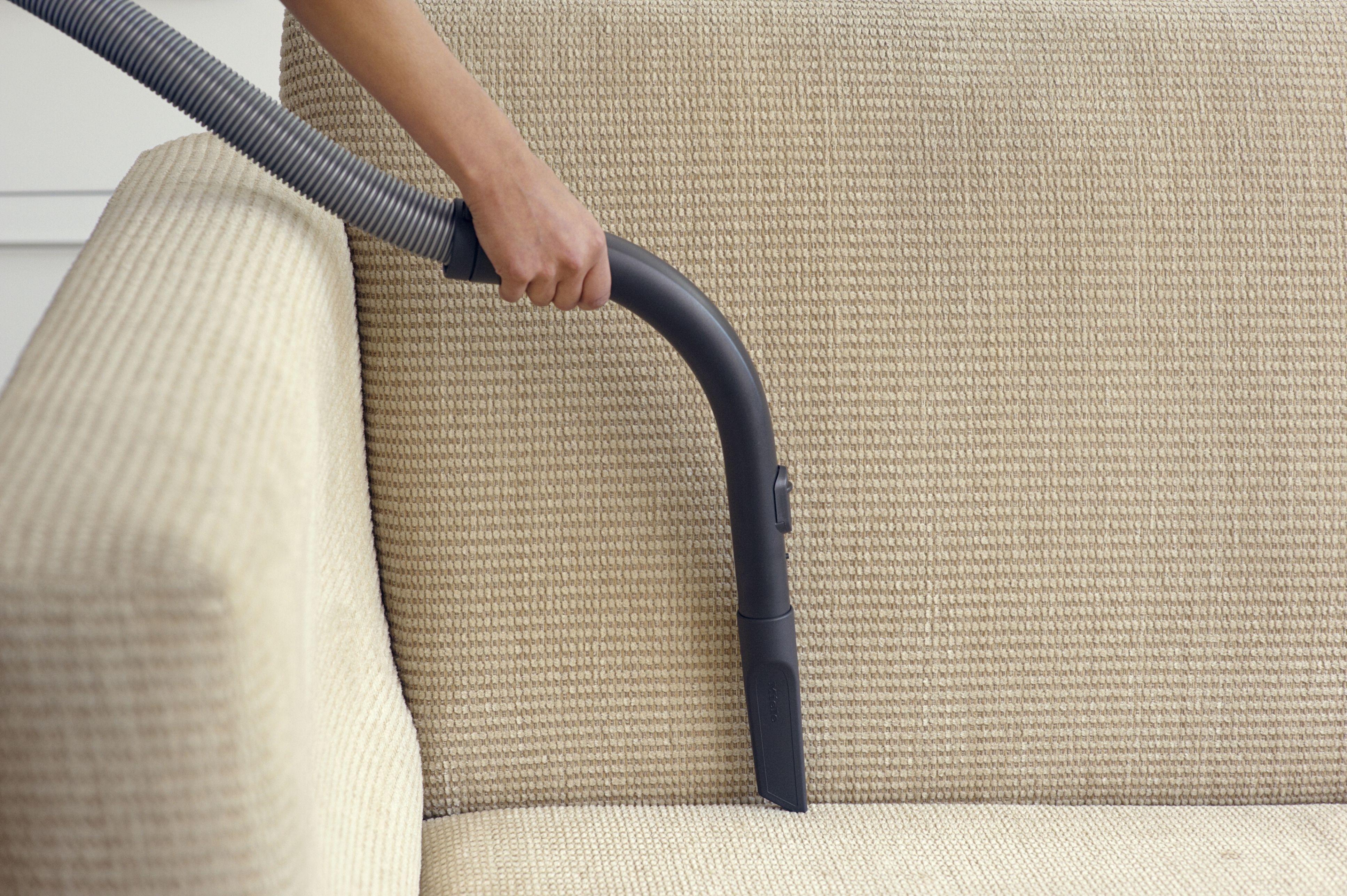 person vacuuming a sofa