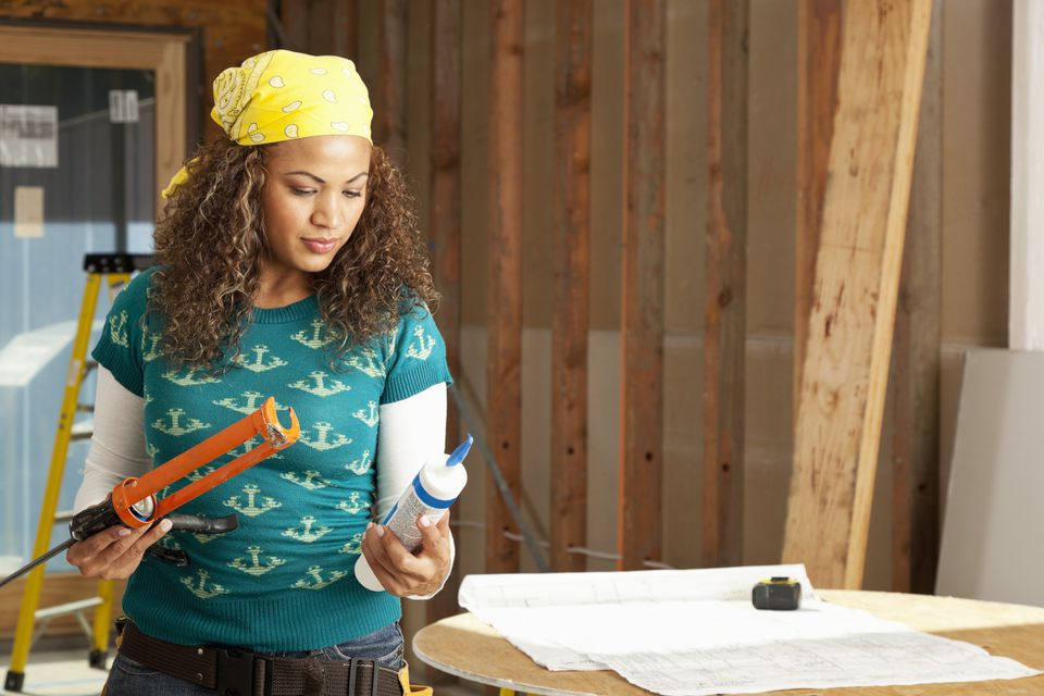 woman holding caulking tube