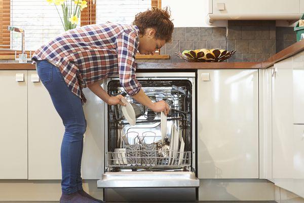 Woman unloading dishwasher in kitchen.