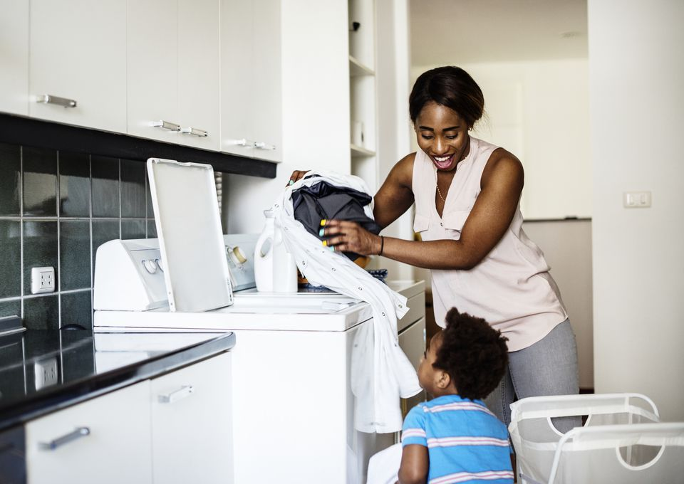 African descent kid helping mom doing the laundry