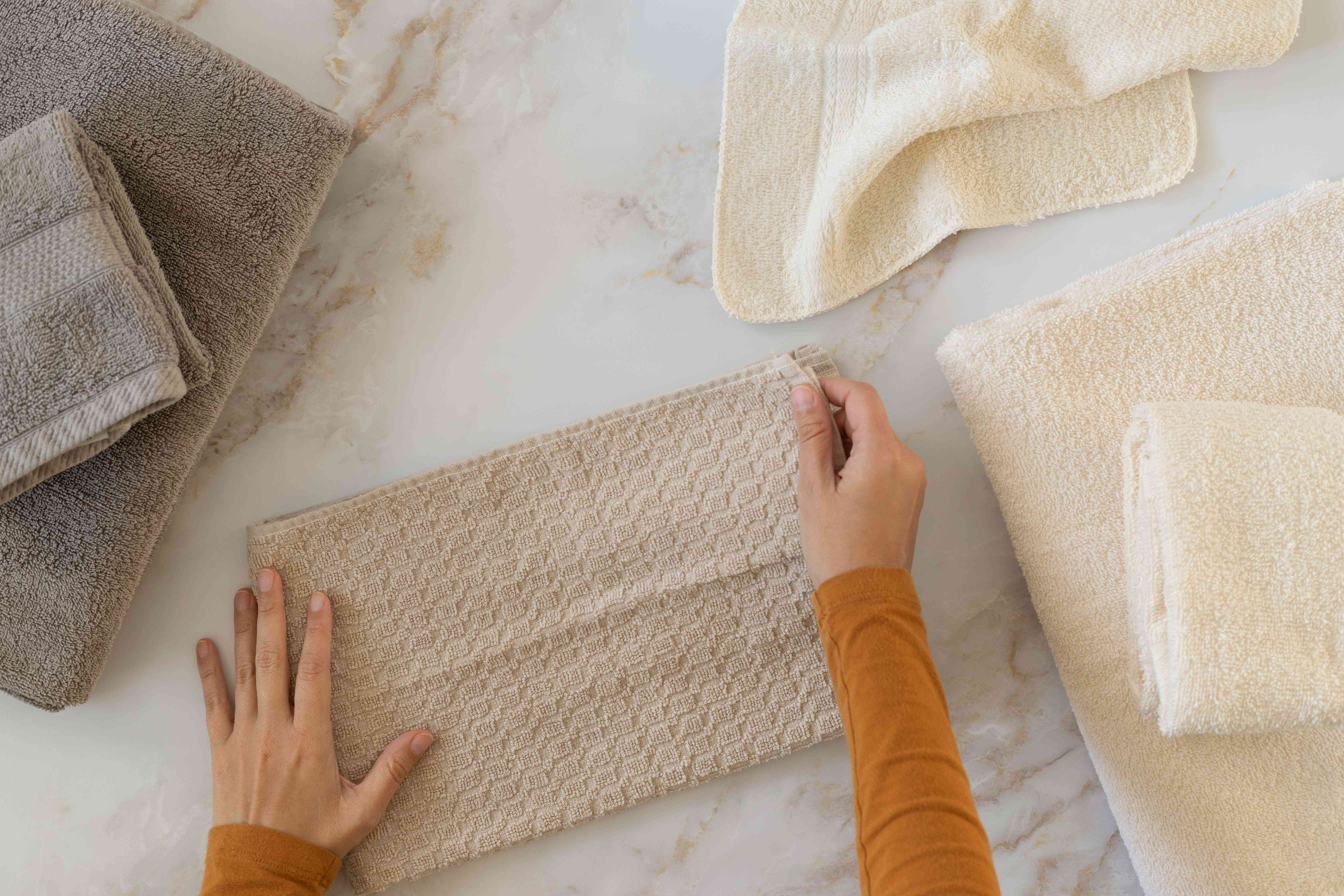 Cream, tan and gray towels sorted by size