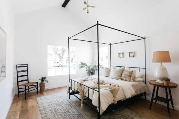 bedroom with white walls and high ceilings, wooden floor with simple woven rug, wooden nightstand, four post bed frame, neutral colors