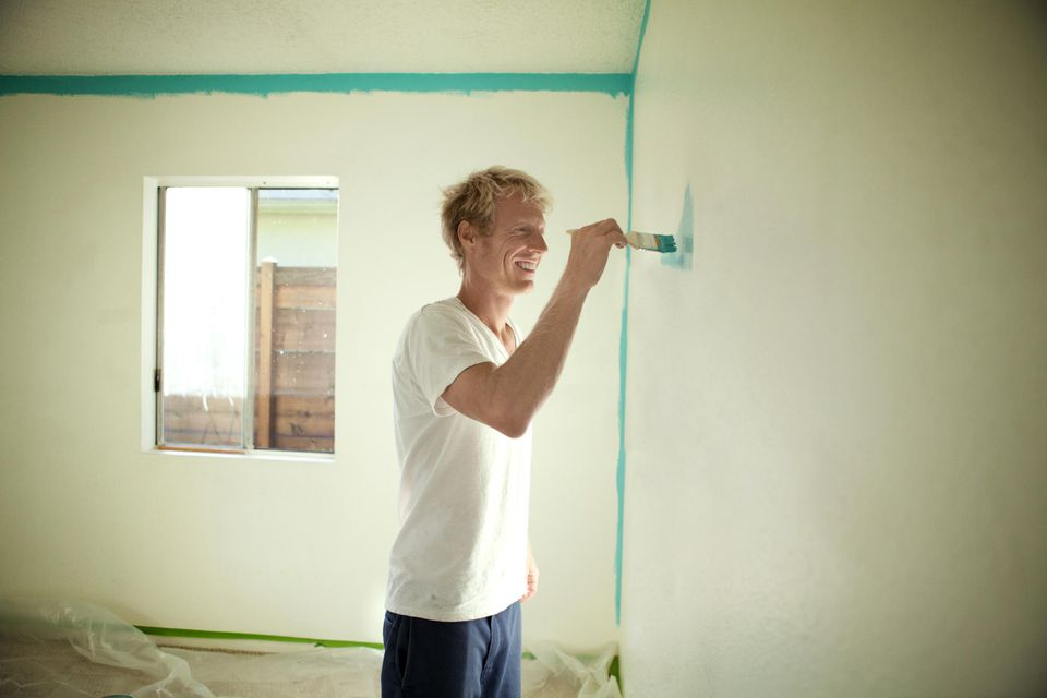 Man Painting wall in new home