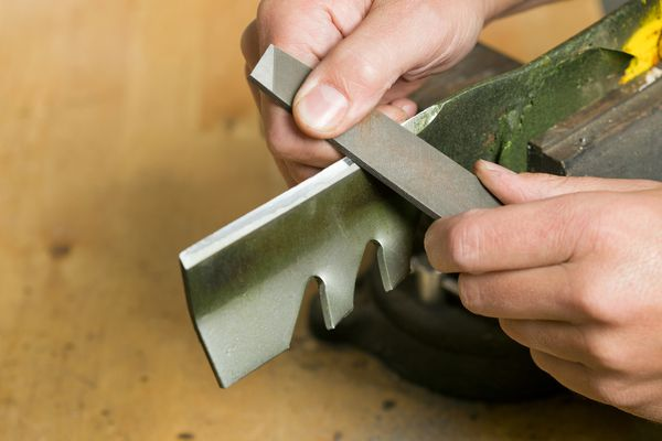 Person filing a mower blade to sharpen it.