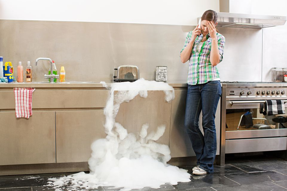 woman calling, clogged sink drain, suds everywhere
