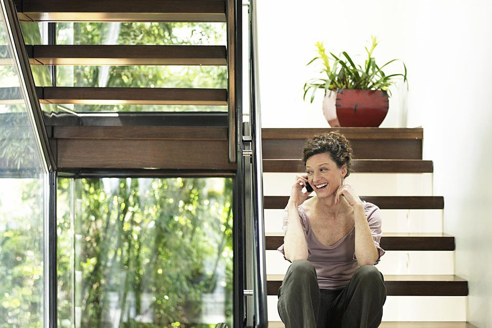 Mature woman sitting on stairs using mobile phone, smiling